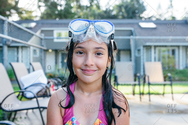 A girl wearing goggles after a swim in the pool