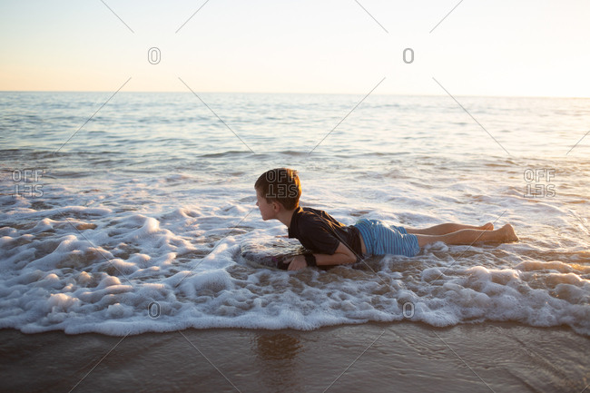 Boy lying on body board as surf rolls in at the beach