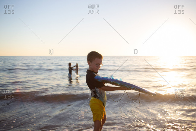 Boy holding a body board at the beach