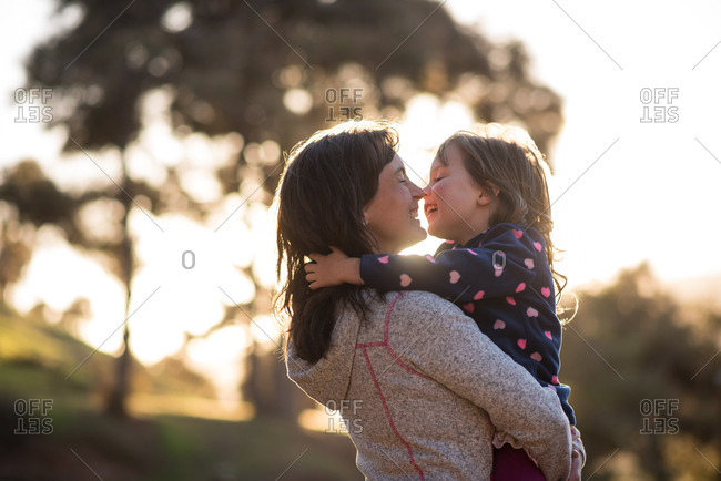Daughter hugging her mother and laughing in nature