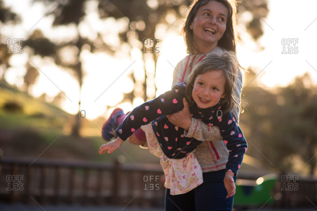 Young smiling mother swings daughter at a playground