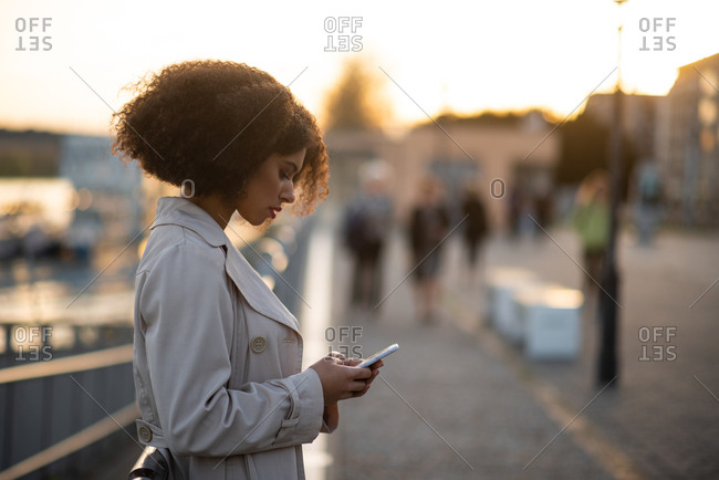Sad young African-American teen looking at her phone in street