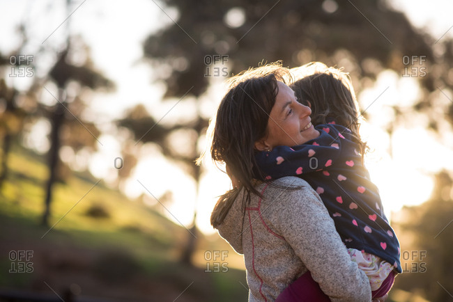 Young mother holding and hugging her little daughter in a park