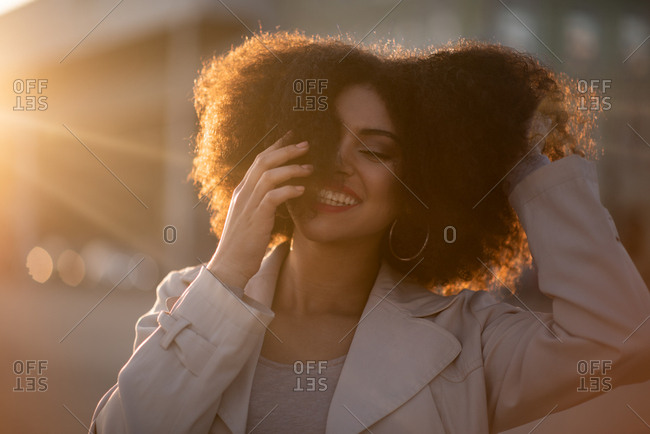 Black teen playing with hair at sunset