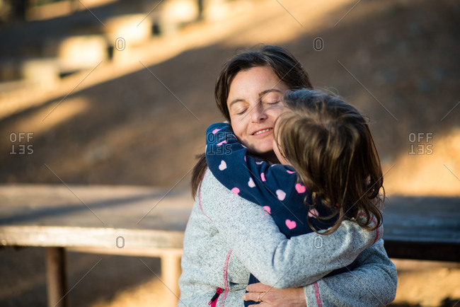 Young mother hugs her little daughter in a park