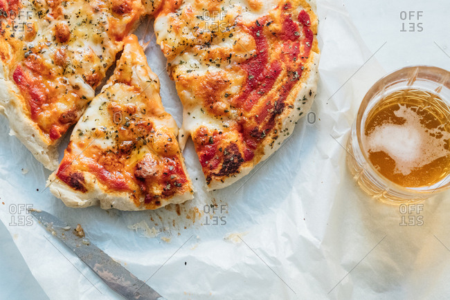 Sliced homemade pizza served with a glass of beer