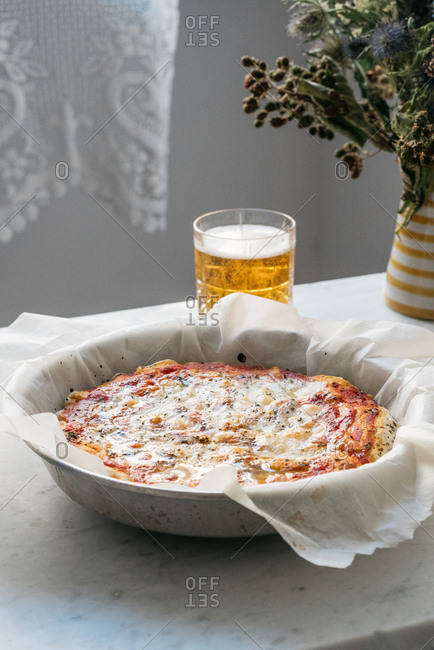 Whole freshly baked homemade pizza in a pan served with a glass of beer