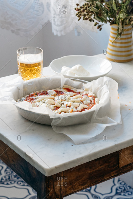Homemade uncooked pizza on table with fresh mozzarella and beer
