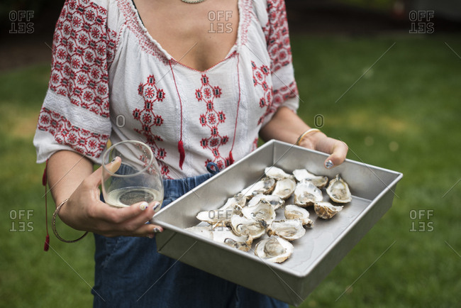 Woman holding a tray of oysters with glass of wine at picnic
