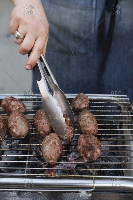 Hands turning over meatballs on a grill with metal tongs