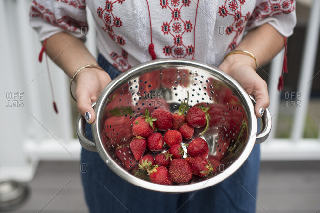 Woman holding a strainer of strawberries outside