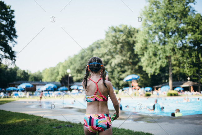 Back view of girl in bathing suit standing in front of crowded outdoor pool