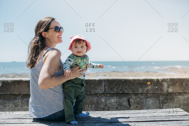 France- content mother and baby girl on a bench at beach promenade