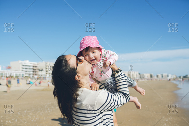 France- La Baule- mother kissing happy baby girl on the beach