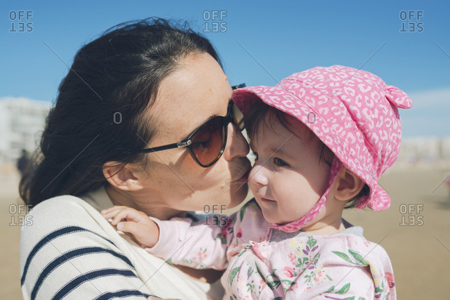 Mother kissing baby girl on the beach