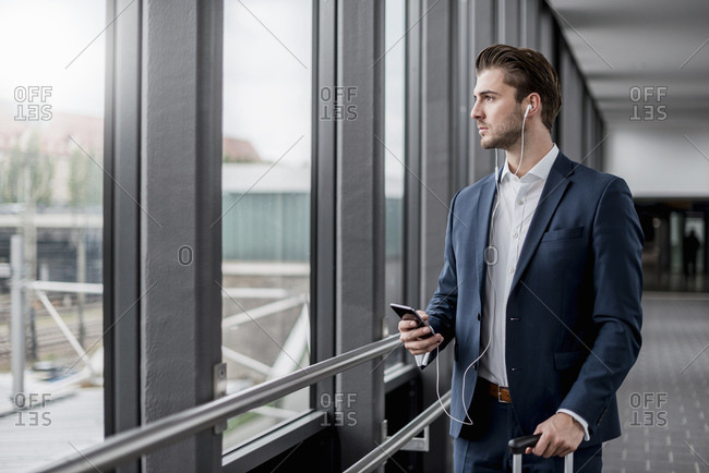 Young businessman in a passageway with cell phone- ear buds and rolling suitcase