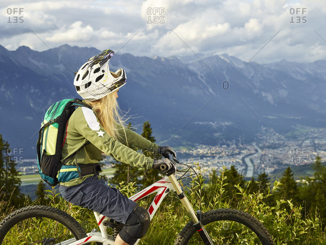 Austria- Tyrol- female downhill mountain biker looking into valley