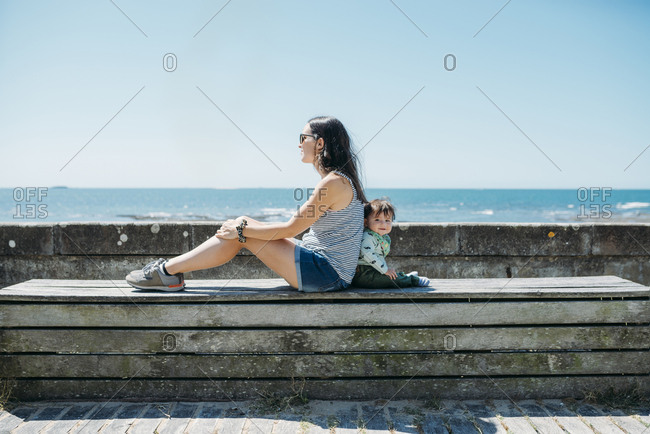 France- mother and baby girl sitting back to back on a bench at beach promenade