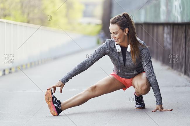 Female runner stretching legs during urban workout