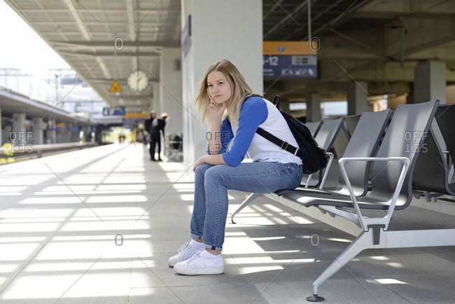 Young woman waiting on bench of a platform in Berlin