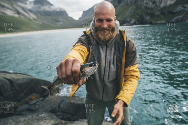 Norway- Lofoten- Moskenesoy- Young man holding freshly caught fish
