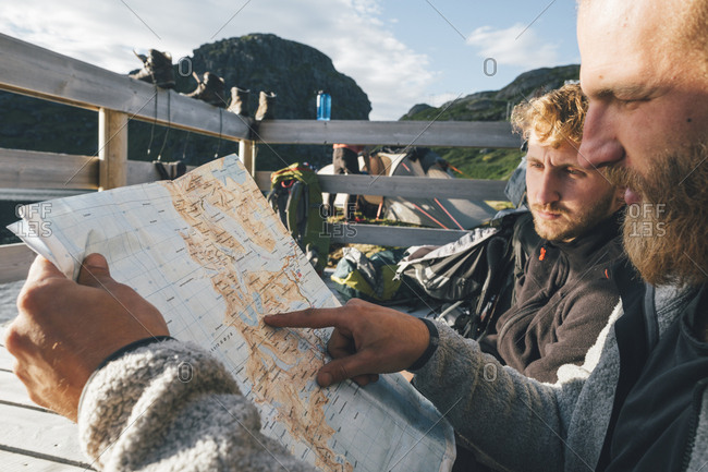 Norway- Lofoten- Moskenesoy- Young men discussing directions- holding map