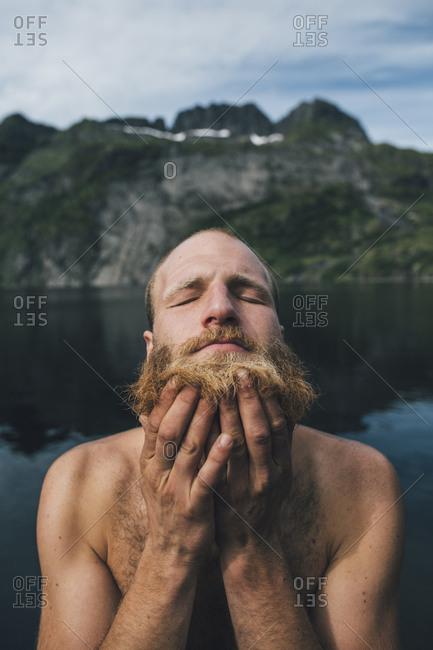 Man washing his beard at a lake with eyes closed