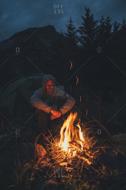 Norway- Lofoten- Moskenesoy- Young man sitting at camp fire
