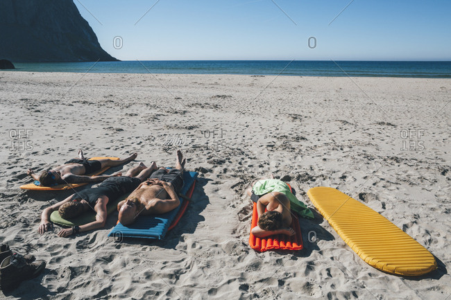 Norway- Lofoten- Moskenesoy- Friends sunbathing on Kvalvika Beach