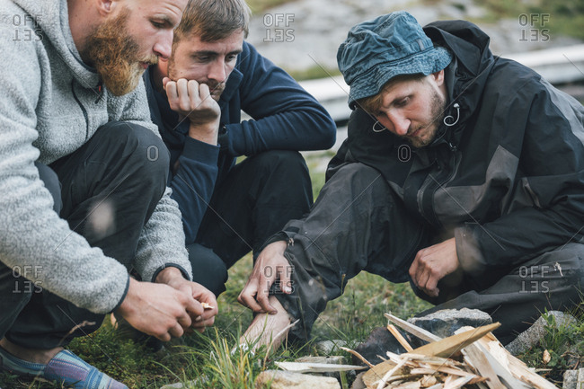 Norway- Lofoten- Moskenesoy- Young men starting a camp fire