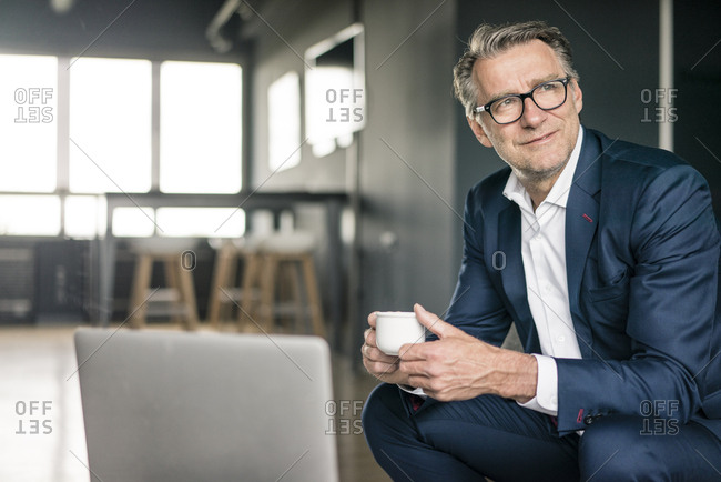Smiling mature businessman with cup of coffee thinking