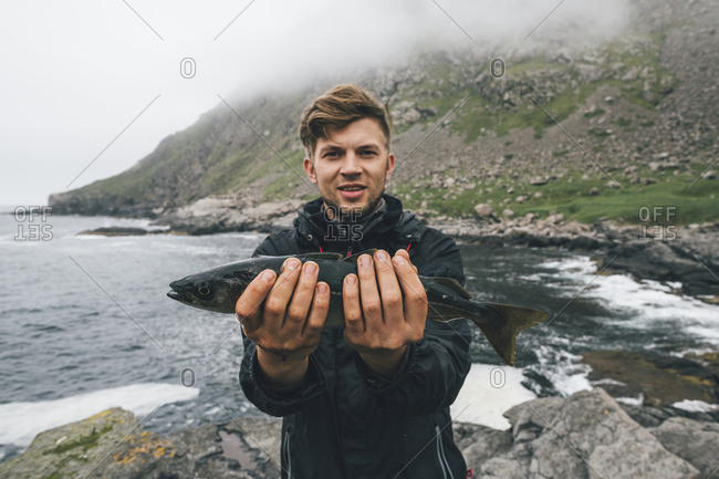 Norway- Lofoten- Moskenesoy- Young man holding freshly caught fish at Horseid beach