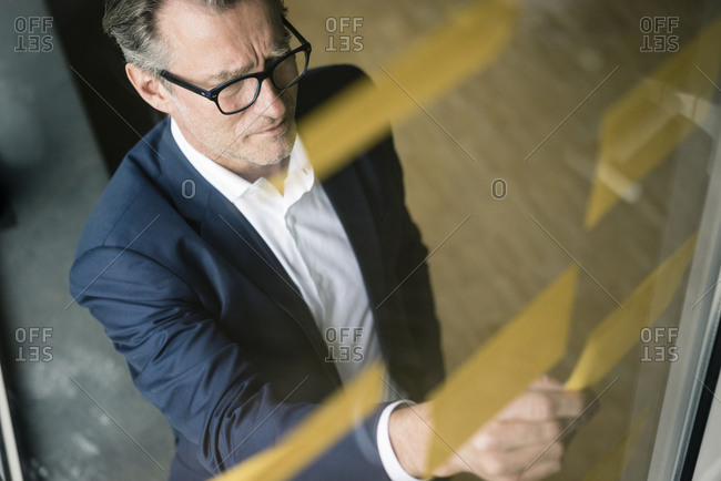 Serious mature businessman looking at sticky notes at glass pane in office