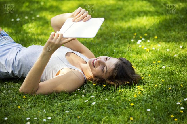 Young woman lying on meadow- using tablet