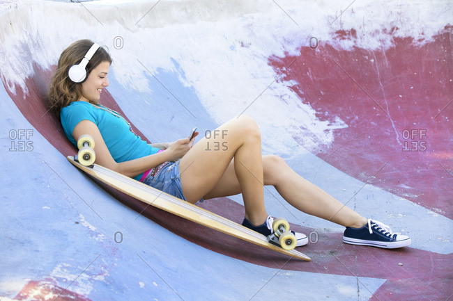 Female longboarder with earphones lying in halfpipe