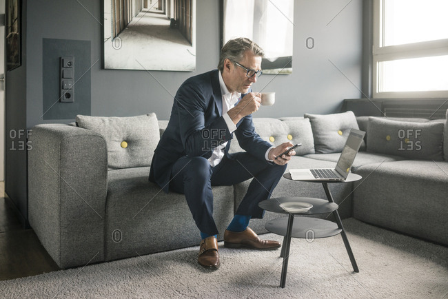 Mature businessman with cup of coffee and laptop using cell phone on couch