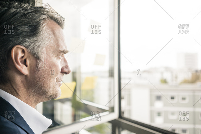 Serious mature businessman looking out of window