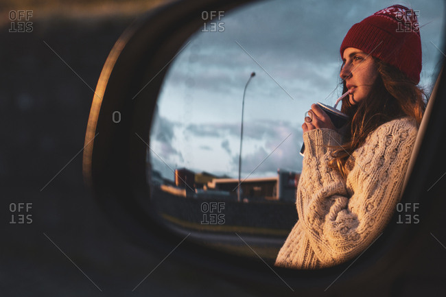 Iceland- young woman with coffee to go at sunset- mirrored in wing mirror