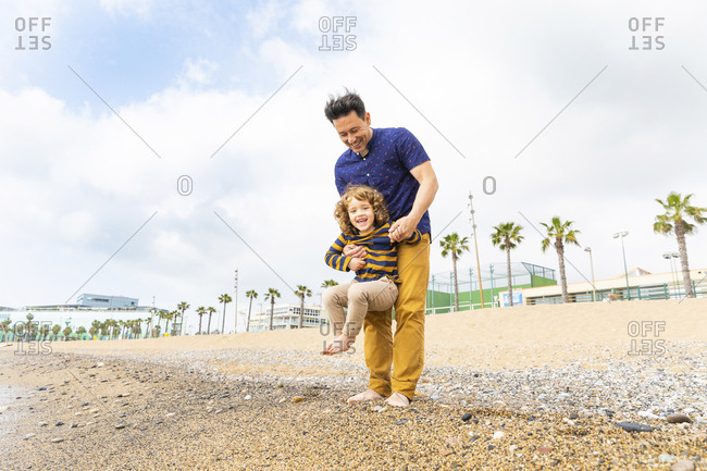 Spain- Barcelona- father holding his son on the beach