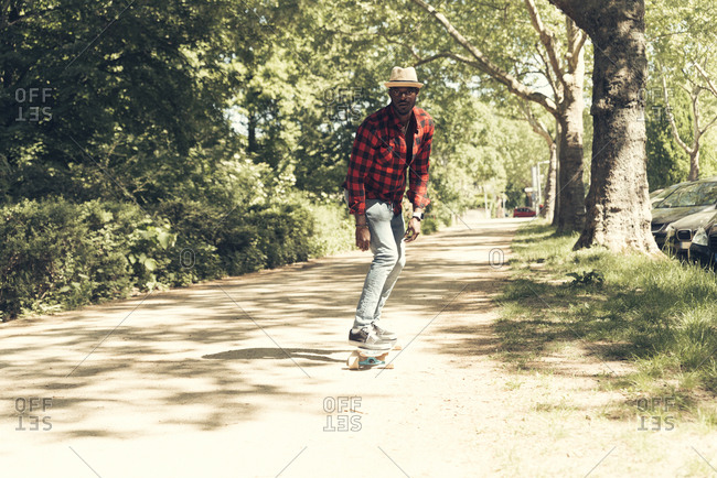 Cool young man skateboarding in park