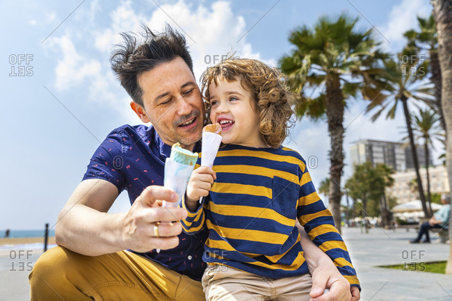 Spain- Barcelona- father and son enjoying an ice cream at seaside