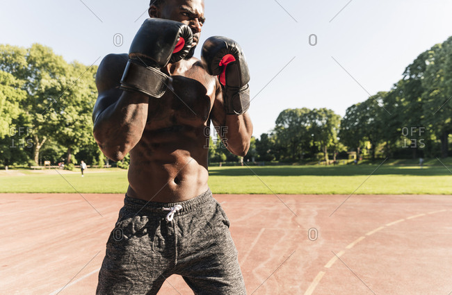Young Afro-American man training boxing on sports field- outdoors