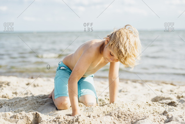 Blond boy playing with sand on the beach