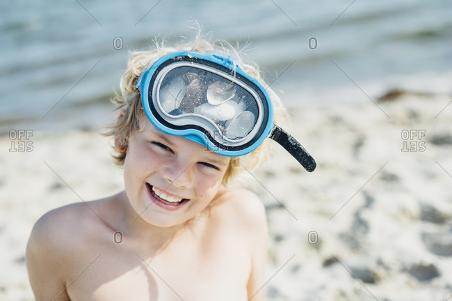 Portrait of happy boy wearing diving goggles on the beach