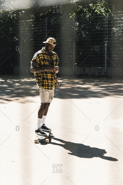 Cool young man in skate park- using smartphone