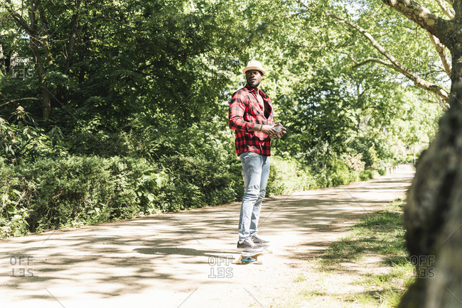 Cool young man skateboarding in park- using smartphone