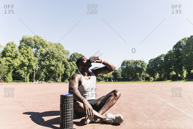 Young athlete sitting on sports field- drinking water