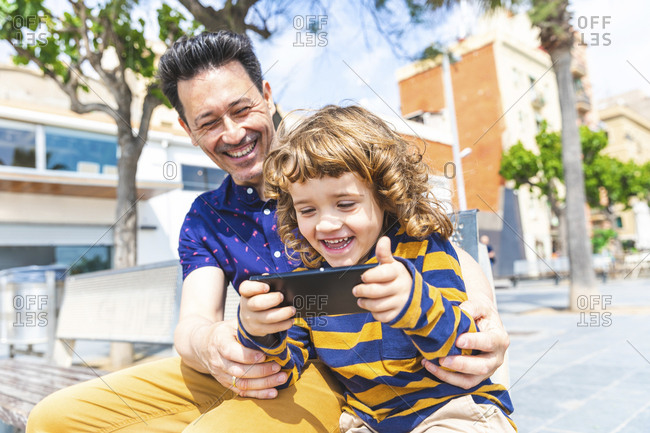 Spain- Barcelona- happy father and son with a smartphone sitting on bench