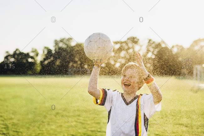 Boy wearing German soccer shirt screaming for joy- standing in water splashes