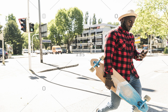 Cool young man with skateboard walking in the city- using smartphone